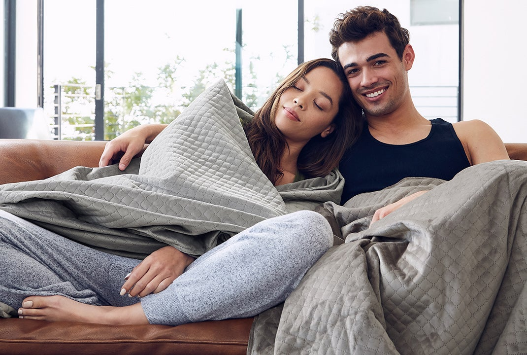 happy couple relaxing with weighted blanket
