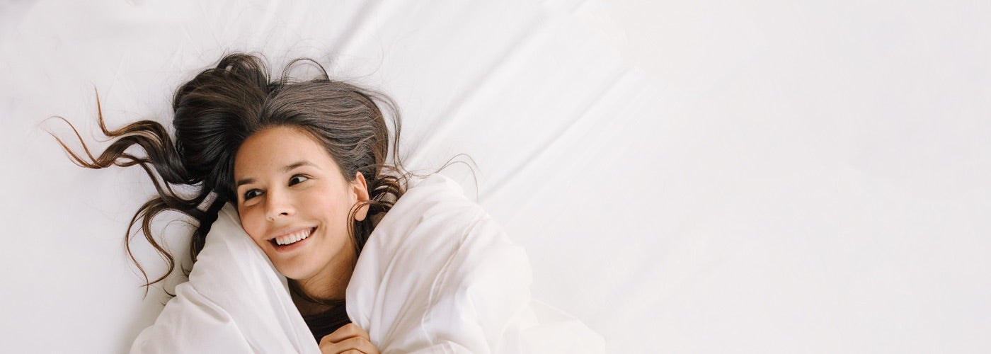 Smiling girl on a white bed - Nectar Sleep